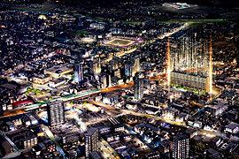 【現地周辺空撮】2016年4月撮影の写真にCG加工を施したもので、実際とは多少異なります。また光の柱は現地の位置を示すためのものであり、建物の高さ、規模を示すものではありません。