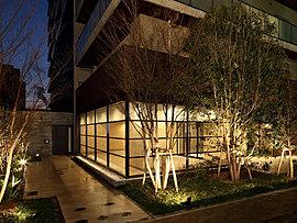 外部に開かれたガラス張りのエントランスホールから漏れる光が、住まう方をあたたくお出迎えするエントランスアプローチ。