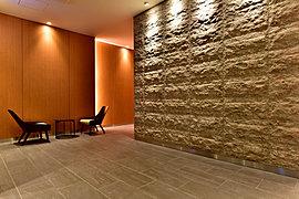 エントランス正面には外観で使っている石をアイストップにして上品さの連続を図っています。ホールを進むと木彫の光る壁の連続が上質なあたたかみをもって優しく住戸へ誘います。