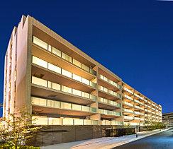 中低層の住宅街を見晴らすように佇む建物東側のファサードには邸宅としての品格を求めました。PRC構造によるスクエアなフォルムを活かし、縦横のラインが美しいグリッドを描くようデザイン。タイルなどの素材の色調に変化をつけて奥行きのある表情を創出。