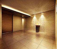 エントランスホールは間接照明で、穏やかで落ち着いた空間を演出しました。また、2種類の磨き加工を施したライムストーンを採用して、素材感が感じられる工夫をしています。