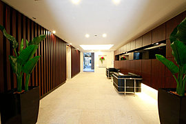 上質感あふれる天然石で、床・壁を設えたゆとりあるエントランスホールは、折上天井とダウンライトによる演出や、木調の縦格子が醸し出す豊かな表情により忘れがたい風景となる、このレジデンスを象徴する空間。