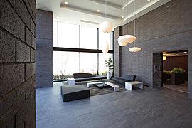 高い天井とガラスウォールが奏でる、伸びやかな開放感。大きな壁面を彩るタイルの重厚感と、床に張り巡らせた大判タイルが醸し出す優雅な品格。見あげれば、アートのようなペンダントライトの光輝く存在感。