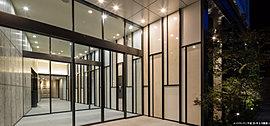 水平に伸びた大庇が、ファザードの垂直ラインを強調。壁の左側を御影石仕上げ、右側を多素材での仕上げと、非対称な意匠の「ウエルカムウォール」が人をもてなすエントランス。