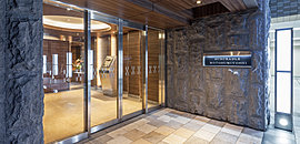 エントランスを纏う外壁は、石の持つ天然の美しさに加え、さらに力強さを表現するコブダシ仕上げの御影石で重厚に設えました。床面には柔らかなベージュ色のタイルを採用。