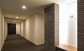 内廊下は外から閉ざされ快適さに満ちた上質なプライベート空間。間接照明による穏やかな空間が私邸へと導きます。
