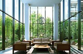 大きな窓から光が差し込む2層吹抜けの開放的なラウンジです。窓の外に広がる中庭の緑が、住む人、訪れる人を出迎えます。