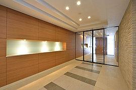 エントランスホールはアースカラーのタイルと木目調の素材を用いた、上質な心地よさを感じるデザインを施しました。