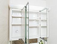 色々な角度で姿を見られるワイドな三面鏡は、裏側が丸ごと便利な収納。センターミラーには、湯気でくもりを防ぐ電熱式ヒーターを組み込んでおります。