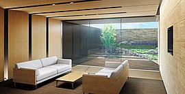 ガラスウォール越しにロビーガーデンの緑とたっぷりの陽光を取り込むエントランスロビー。壁面、天井、家具の木目調がナチュラルモダンな雰囲気で、ゆったりとしたひと時を過ごせます。