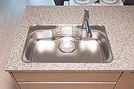 ミドルサイズのシンク中央にくぼみがあり、大きな鍋を洗う際なども楽。水ハネ音やスプーンなどの落下音を軽減する静音タイプです。