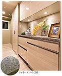 キッチン空間とトータルにコーディネートした食器棚を設置。天板は、93%が高純度の水品で出来ているフィオレストーン。便利なカウンター付きです。
