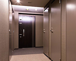 風合いのあるクロスの壁とやさしい間接照明が、ホテルのような落ち着いた雰囲気をかもす共用廊下。