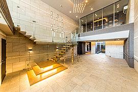目指したのは、美術館やホテルのような開放感。2層の高さと広々としたスペースを贅沢に使った、開放感漂うエントランスホール。2階には自由にご利用いただけるラウンジスペースやライブラリースペースを設置しています。