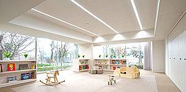 住まう人たちがコミュニケーションをとる集会場や子どもたちが元気に遊ぶキッズルームなど、様々な用途に応えるマルチな空間。窓の向こうには緑あふれるガーデンが広がり、室内は陽光と開放感に満ちています。