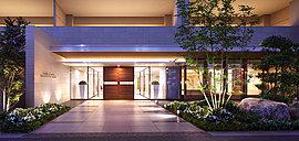 緑豊かなフロントガーデンに包まれたアプローチを通って、建物の品格を語りかけるエントランスへ。正面に温かみのある木調扉を配置し、穏やかな照明で満たしたガラス張りの空間が、訪れる方を私邸領域へとエスコートします。