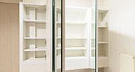 大きな三面鏡の裏側を、洗面小物などを収納できるキャビネットに。※キャビネット下には、一部多孔質タイル(エコカラット)を採用