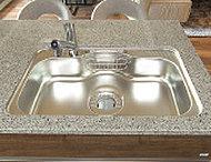 制振材の効果により水はねの音を軽減する静音仕様のシンク。中央にくぼみをつけて、中華鍋なども洗えるスペースを確保しました。