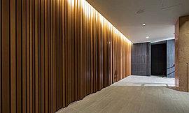 語らいの時をより優美に。エントランスホールと連続するラウンジ空間は波打つ木調ルーバーの壁面と大理石の壁が調和した気品ある空間として設えています。