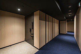 内廊下には木調パネルをランダムに並べ、廊下壁面に陰影とリズムをつけました。日本家屋の要素を取り入れ、さらに格式ある深みを生み出しています。