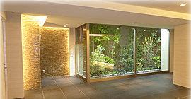 来客を歓迎する場所に相応しい上質な空間となるよう、デザインと素材の一つひとつに吟味を重ねたエントランスホール。やわらかな自然の光を取り込む大きなガラス壁を隔てた「小さな杜」には、四季を身近に感じられるよう様々な花木をご用意。