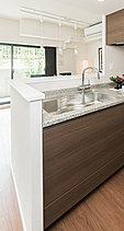 システムキッチンの収納扉は、木目調の質感をフローリングと統一しながらも、より深みのあるブラウンカラーを採用。さらにフィオレストーン天板で、インテリアとしての美しさを高めました。
