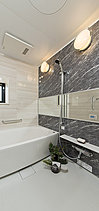 心身をリラックスさせるバスルームは、ラグジュアリーなくつろぎをもたらす空間をデザイン。色味と表情が異なる石目調の壁パネルを張り分け、ホテルライクなリラクゼーションスペースを創出しました。