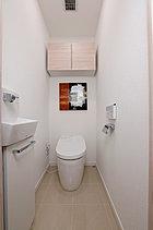 スマートなタンクレストイレは、清潔さにこだわった快適なウォシュレット付き。スペースを取らない吊戸棚や、快適にお使いいただくため手洗器も設置しました。(施工例)