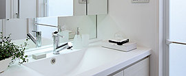 一日を始めるパウダールームには、洗練された印象のカウンター一体型洗面ボウルや三面鏡裏収納を採用しました。