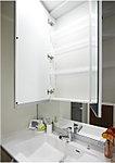 洗面化粧台には、三面鏡スタイルを採用。鏡の裏には、化粧品や小物が収まる便利なスペースを設けています。