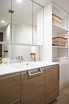三面鏡が広がりを演出するクリーンなドレッシングルーム。洗剤や化粧小物なども充分な収納ですっきりとした空間に。家族誰もが使いやすい機能性にあふれています。