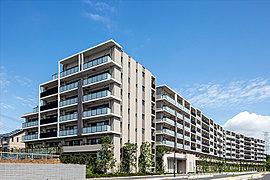 緑に包まれ、道路面から約3m高い「台座」に凛々しく建つのは水平と垂直ラインによる精緻な直線で描かれる全182邸の壮大な建築。めざしたのは新たな街の、新たな暮らしの象徴となる住まいの新基準。