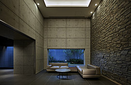 エントランスホールの壁の石の風合いを活かし、折り上げ天井には間接照明とダウンライトを採用して、全体をモダンなデザインで仕上げた空間には、深いくつろぎの時間が流れています。