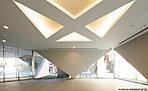 印象的な建築美に目を奪われるエントランスホール。コンクリート打ち放し風の壁や、光と緑を取り入れる大きな開口、そして折り上げ天井まで。三角形で創られたデザインが一体化するような美しい空間を創出しました。