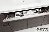 洗面ボウル前のデッドスペースを有効活用し、メイク用品などの小物を収納できるポケット。