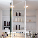鏡裏に大容量の収納スペースを設けた、大型の三面鏡。中央の鏡にはくもり止めを採用しています。