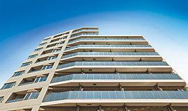 南側に第一種低層住居専用地域が広がる立地を活かし、開放感あふれる空へと伸びるスタイリッシュなフォルムに。風合い豊かなホワイト系のタイルと、窓やガラス手摺に映る空の青さが、柔和で洗練された表情を漂わせます。