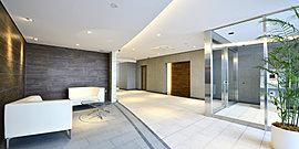 エントランスホールは帰宅の際に安心感を与えるスペースであり、社交の場でもあると位置づけ、伸びやかな広がりを確保し、ソファーでゆったりとくつろげるラウンジスペースも設けました。片側の壁は緩やかな曲線を描く形状とすることで、和らいだ雰囲気を創出