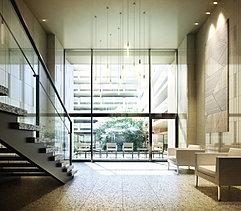 杜のエントランスアプローチの先に広がるエントランスホール。2層吹抜けの大開口ガラスが切り取る、中庭の豊かな緑の風景。石貼の壁面は表面を磨いた箇所に緑を映り込ませることで外と内を結びつけながら空間の広がりを感じさせるデザインを。