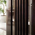 奥深い木目が印象的な建具は、独自の後塗装技術による継ぎ目のない上質な佇まいが特徴。仕上げには鏡面仕上げからやや光沢を抑えた「九分艶」を採用。