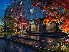 """建物の表情を形成するエントランスは、自然石のステップ、庭園灯、落ち着いた風合いのルーバー庇など""""和モダン""""な設えが、シンボルツリーであるヤマモミジと美しく調和。"""