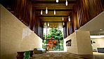 住まう方を迎え入れるのは、2層吹抜けの開放的なエントランスホール。ペンダントライトや木調のルーバー、重厚感のある大判タイルなどにより上質な空間を構成。大きなガラス面から潤い豊かな植栽帯を眺めることができます。