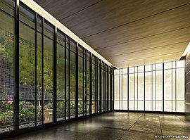 光壁と間接照明の柔らかな光に満たされた空間。和紙調のガラス壁が、昼には繊細な自然光と四季の彩りを、夜にはほのかな灯りに照らされた植栽の表情を、その空間へと招き入れる。