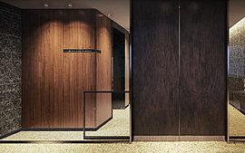 風除室からエレベーターホールは、重厚な質感を漂わせる黒い石と繊細で温かみのある木をそれぞれの壁面に配し、ホテルのような瀟洒な雰囲気を演出。 個性的なマテリアルが競演するなかを優しい光にエスコートされる迎賓空間には、心地よい緊張感が漂っている