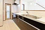 <キッチン施工例> 「食洗機・人工大理石天板・浄水器・スライド収納」など機能性に優れたシステムキッチンを全棟に採用 「パントリー+勝手口設計」で収納・採光・通風を満たすママ目線のキッチンが完成しました