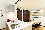 食器洗浄器付きのシステムキッチンは全戸標準装備。壁には備え付けの棚など、収納スペースも充実しています。 (当社施工例)
