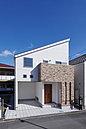【当社施工例】ホワイトの外壁とシャープな屋根が目を引くスタイリッシュな外観。ベージュ系のレンガとウッドのドアがとても良いアクセントになっています。