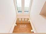 バルコニーに面した窓から入った光は、吹き抜けを通して1階のリビングを優しく照らします。