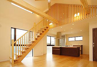 明るい太陽の光が満ち溢れる上階LDK施工例。上の小屋裏階への階段が開放感のある心地のよい空間を更に広々と演出します。