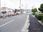当分譲地の前面道路状況の写真です。幅6m2車線公道で、1.8mの歩道が設置されて歩行者の安全・安心が確保され、歩道の外側は、緑と広い空間が拡がる住み良い街並が形成されております。